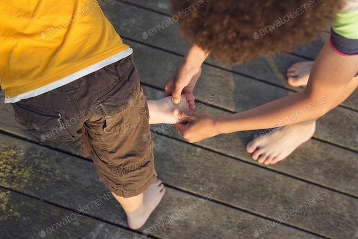 Junge (10-11) untersucht anderen Jungen (4-5) Fuß