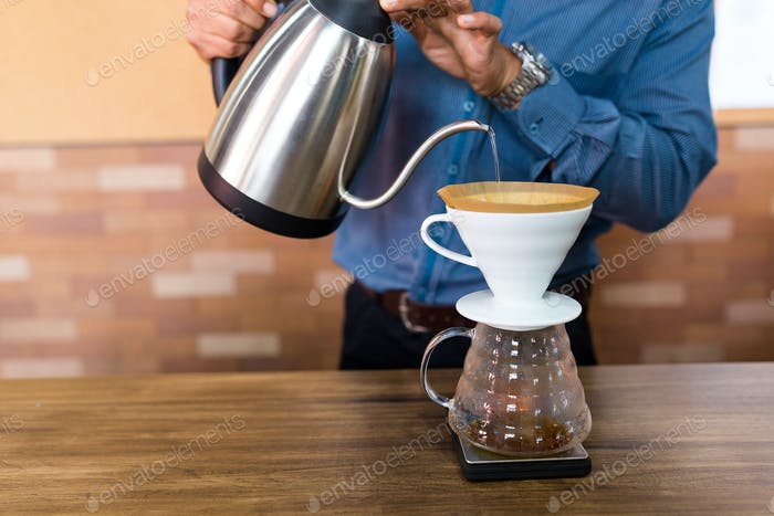 Barista pouring water on coffee with filter in cafe