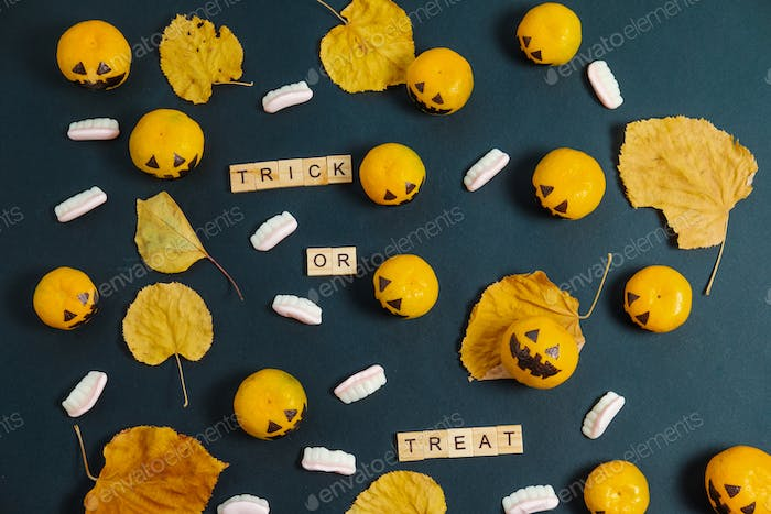 Flat Lay Trick or Treat  Halloween with fake pumpkins and tangerines
