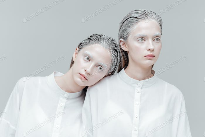 Close-up portrait of two women in smart white shirts