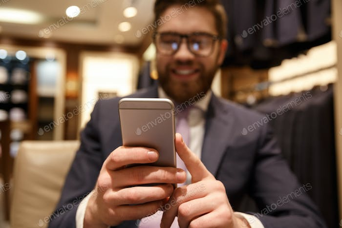 Happy young bearded businessman chatting by phone.