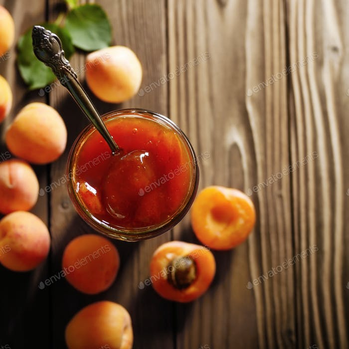 Glass Jar of Apricot jam on wooden table with ripe apricots at b