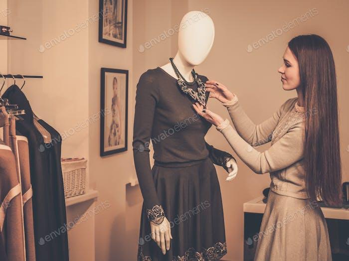 Junge Frau mit Blick auf Halskette auf Schaufensterpuppe im Showroom