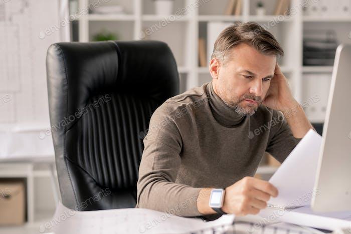 Reife Ingenieur mit Papieren Blick auf eine der Skizzen während Überprüfung sie