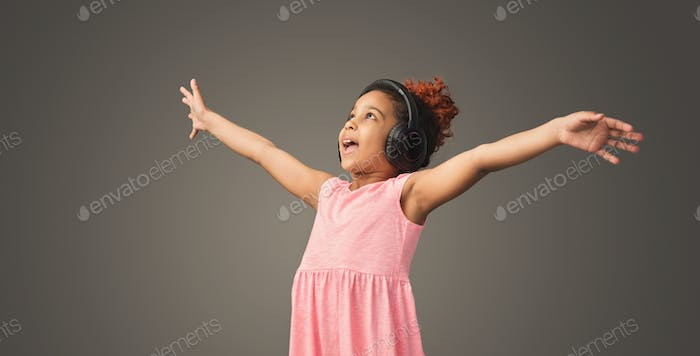 Lovely little girl is dancing in headphones
