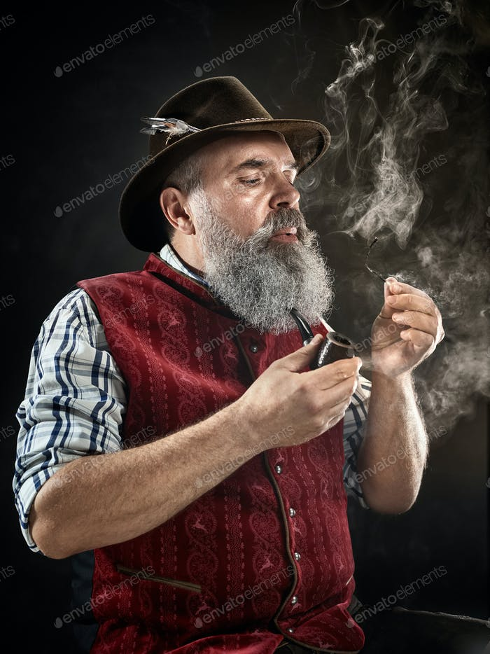 dramatic portrait of senior smoking tobacco pipe