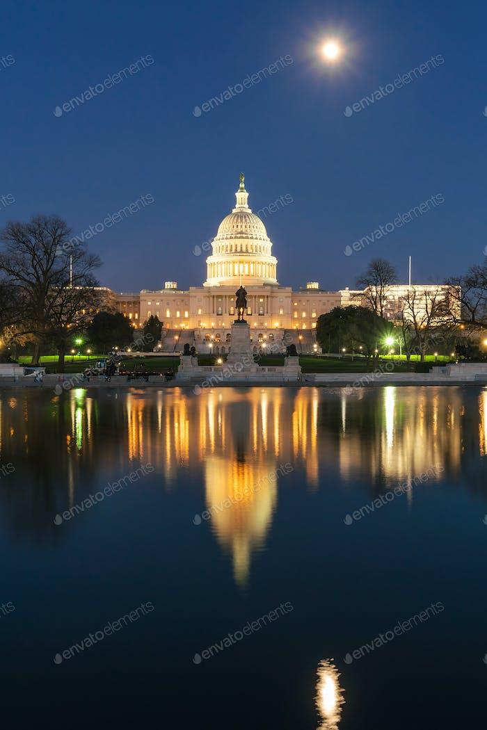 Edificio del Capitolio de los Estados Unidos en la hora del crepúsculo con súper reflexión de luna llena con la gran piscina