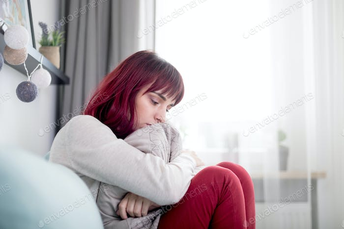 Sad and depressed young woman sitting on sofa at home thinking about unpleasant experiences