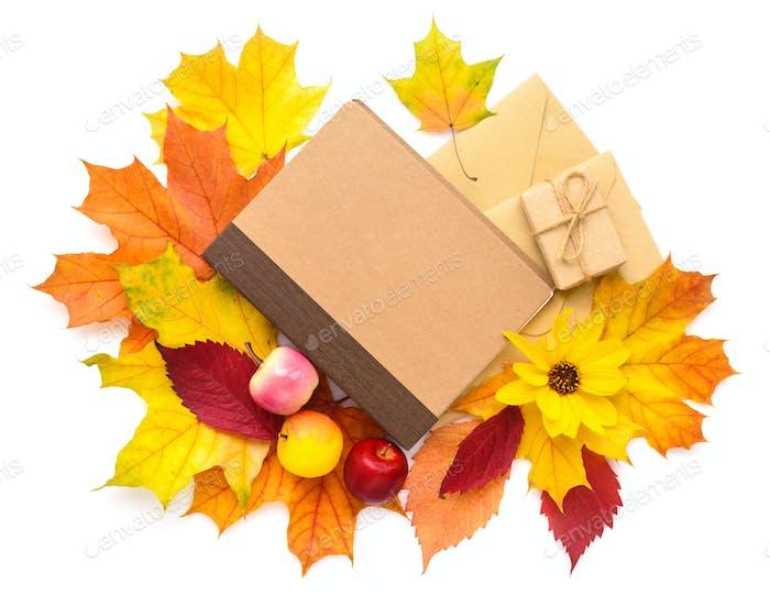 Herbstblätter, Notizbuch und Umschlag auf weißem Hintergrund. Oben