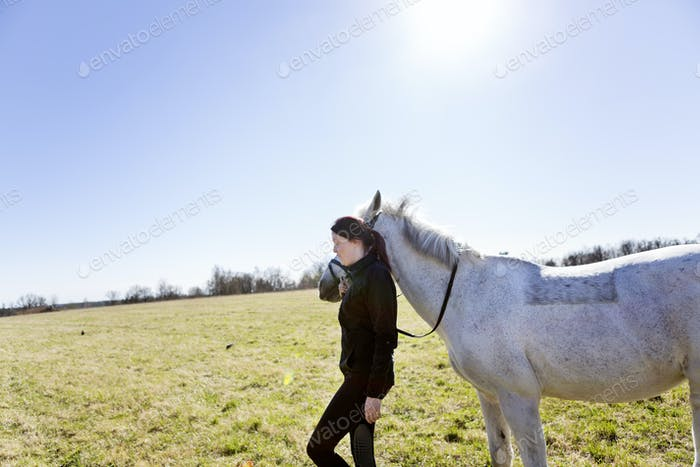 Side view of woman walking with horse on field against clear sky
