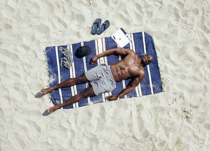 Young guy lying shirtless on a mat sunbathing
