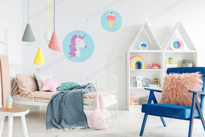 Furry pink pillow on a vibrant blue armchair in a sweet kid bedr