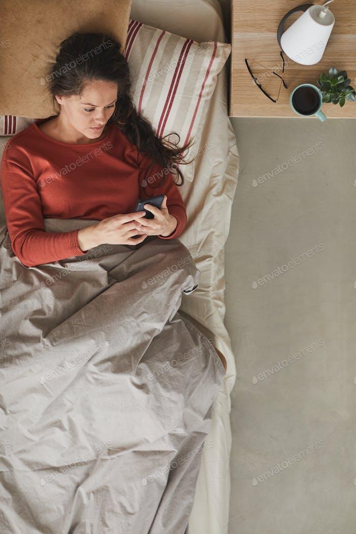 Frau mit Telefon im Bett