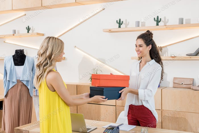 cashier giving shoe boxes to woman