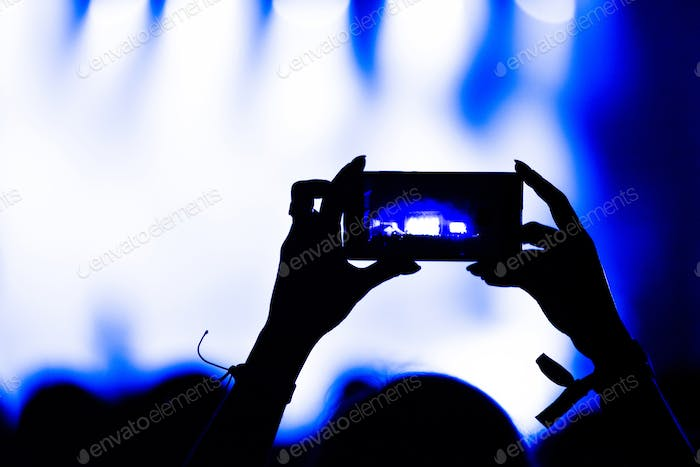 Silhouette of hands recording video with smart phone at music concert