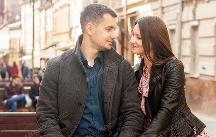 Bonita pareja joven sentada en la calle