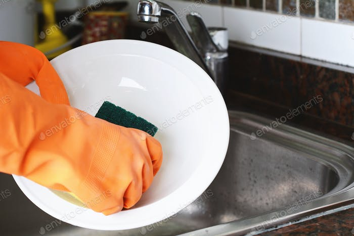 Hands in rubber gloves washing dishes with spon