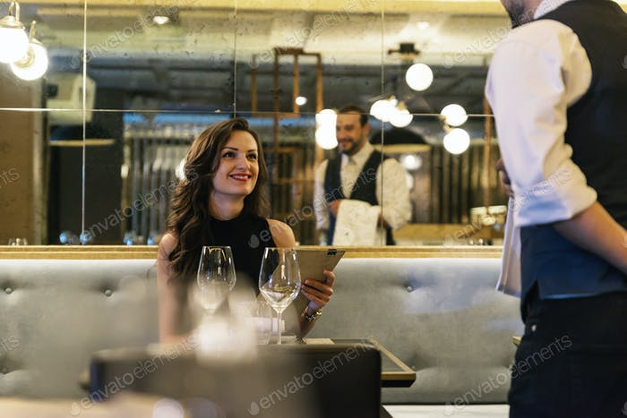 Young attractive woman making order at restaurant