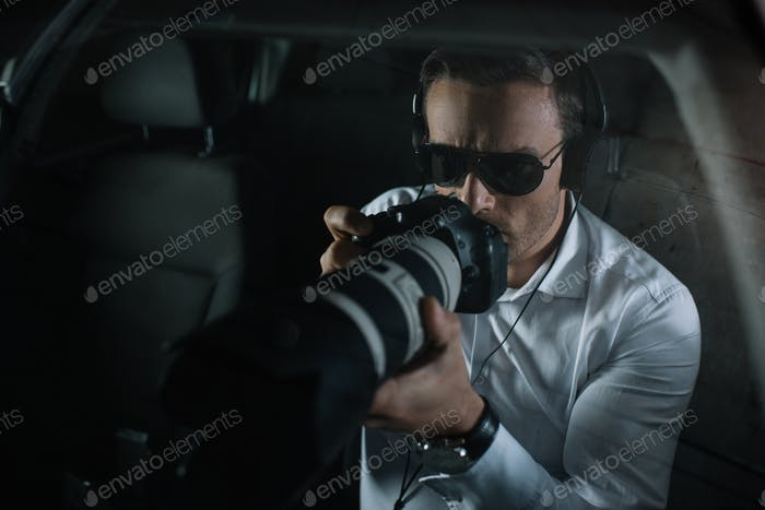 male private detective in headphones doing surveillance by camera with object glass from car