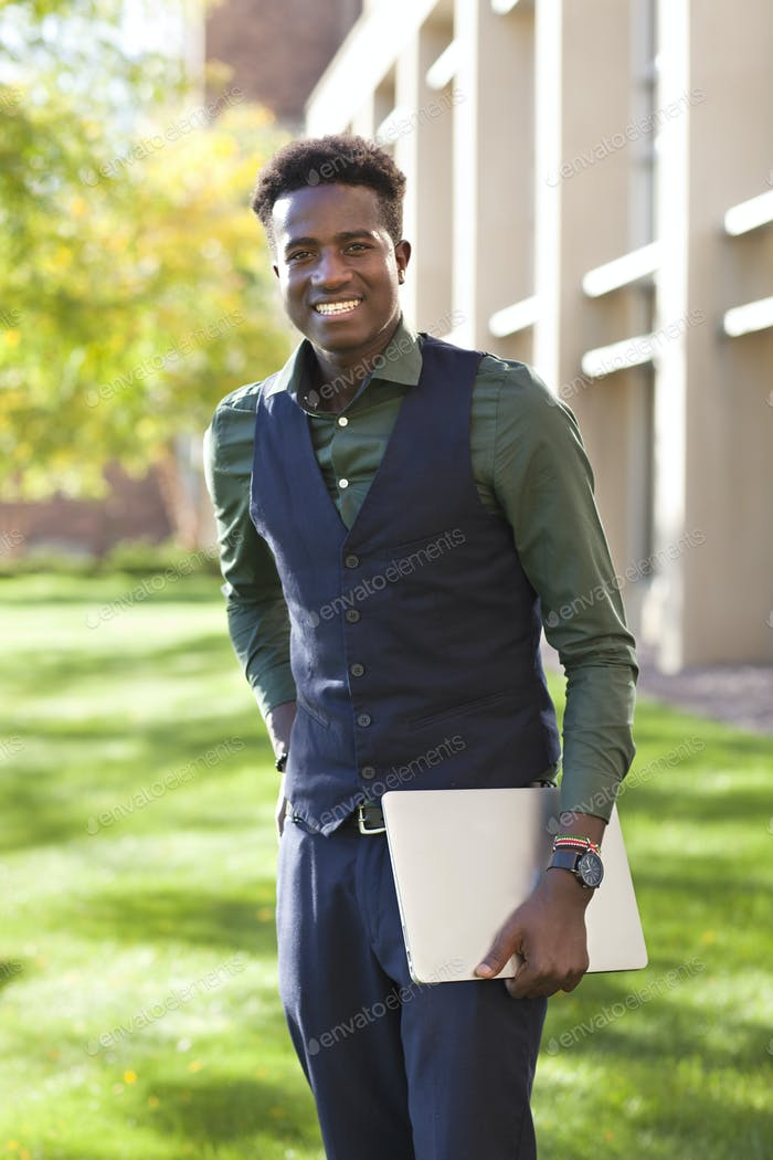 Handsome young black student holding laptop on a school campus