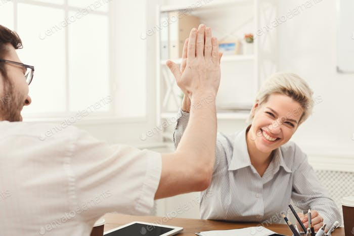 Young happy business partners in office with computer