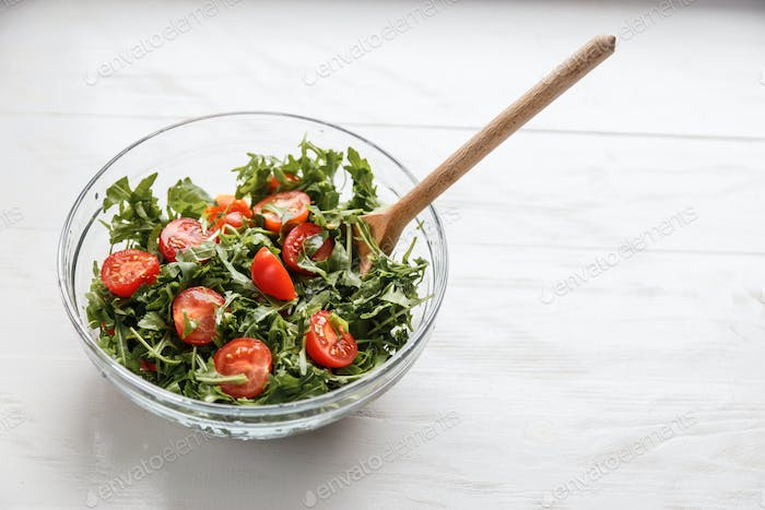 salad with arugula and tomatoes in the glass plate