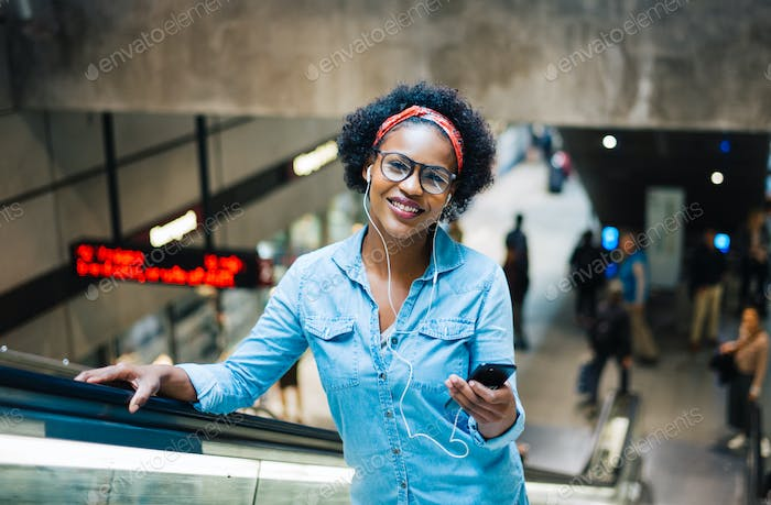 Young woman listening to music on a subway station escalator