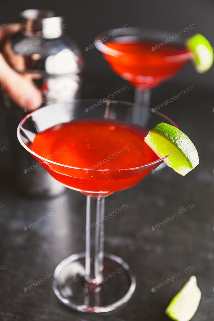 Red cocktail with lime in Martini glass on a table.