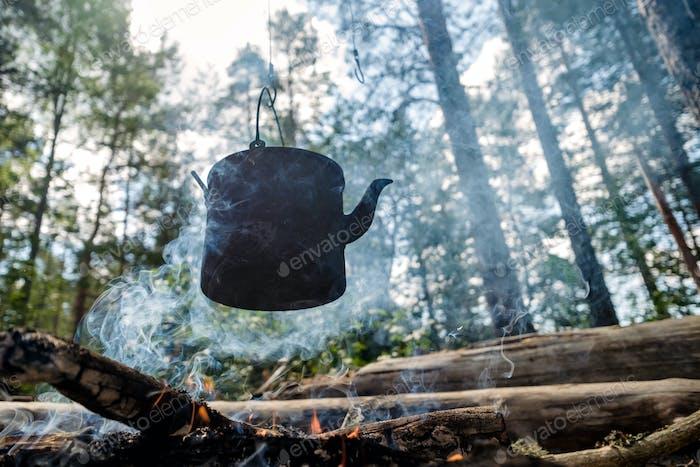 Schwarze Bowler über einem Feuer im Wald. Sommercamp-Touristen.