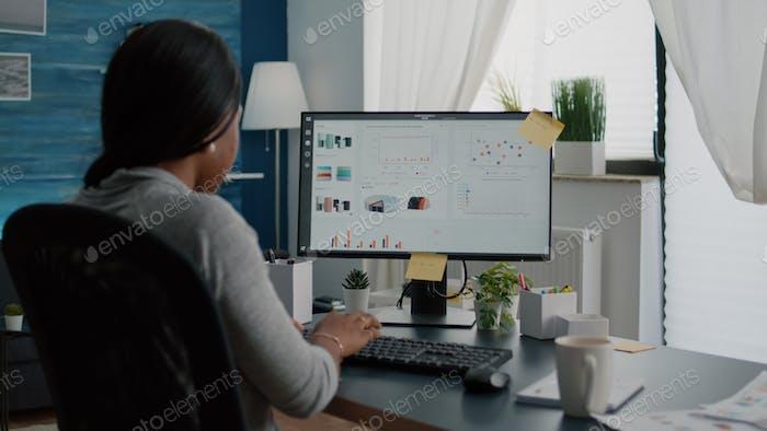 Closeup of black student browsing financial infographics analyzing statistics on laptop