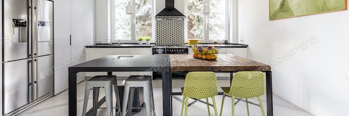 Bright functional kitchen with two tables