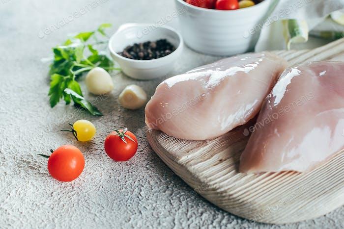 Rohe Hähnchenbrustfilets und Zutaten für das Abendessen auf Holzbrett auf Betontisch Hintergrund