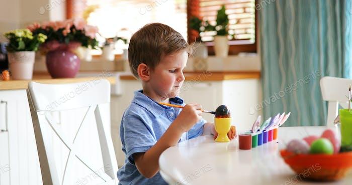 Little kid boy Färbung Eier für Osterferien in der heimischen Küche