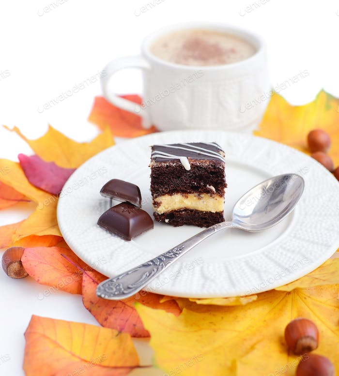 Piece of cake on a plate, chocolate, autumn leaves, nuts and a c