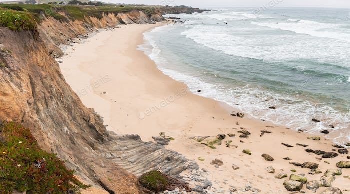 Sandy beach on a cloudy day on the Pacific Ocean coastline, Pescadero State Beach, California