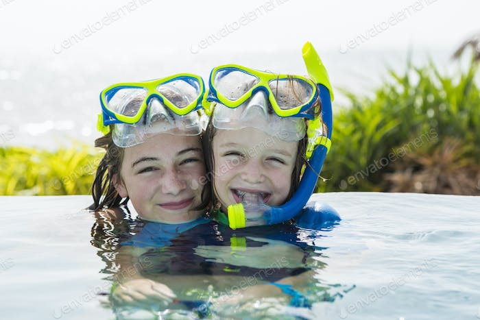 13 year old girl and her 5 year old brotehr in pool, smiling