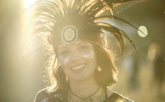 Young woman at a summer music festival wearing feather headdress and face painted, smiling at