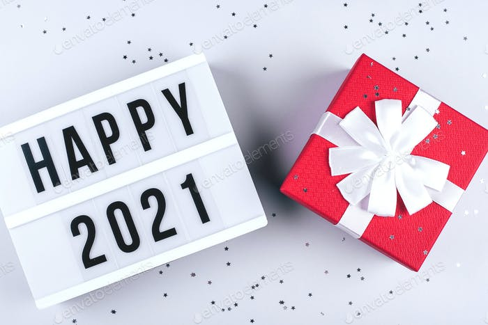 Happy New Year 2021 celebration. Light box with text Happy 2021, red gift present on grey background