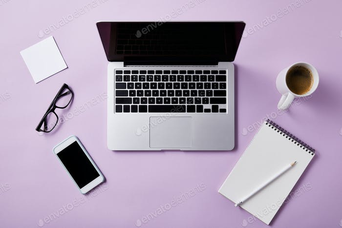 top view of workplace with laptop and smartphone on pink tabletop for mockup