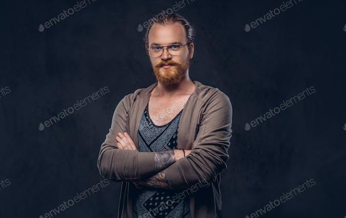 Porträt eines rothaarigen Hipstermännchens in einem Studio. Isoliert auf dem dunklen Hintergrund.