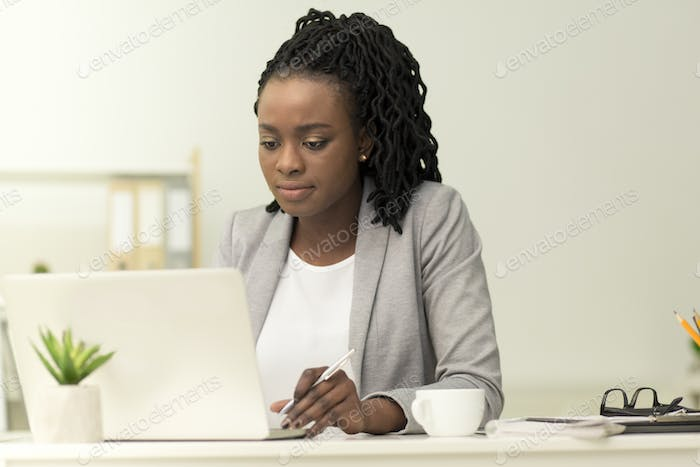 Serious Black Businesswoman Working On Laptop In Office