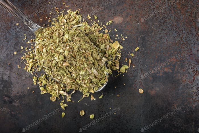 Spoon filled with dried oregano