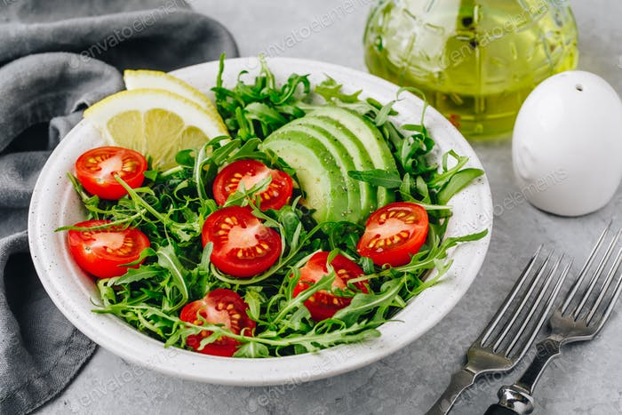 Green salad with leaves of arugula, tomatoes and avocado.