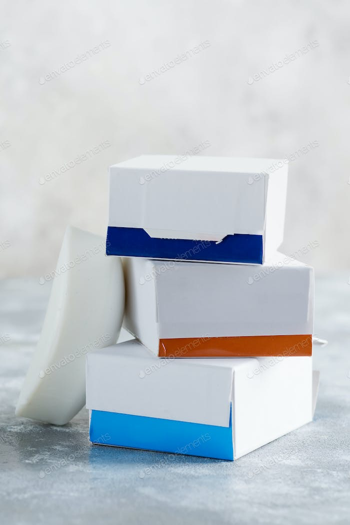 Set from three paper mock up boxes for packaging spa soap products on a marble grey background