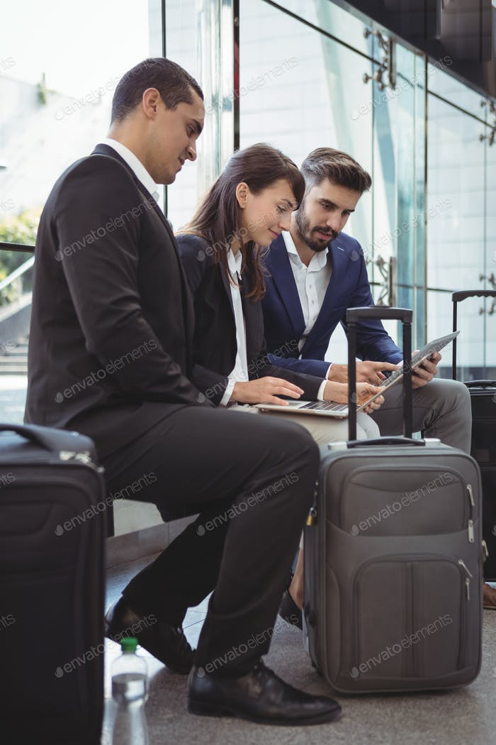 Business executives using laptop on platform