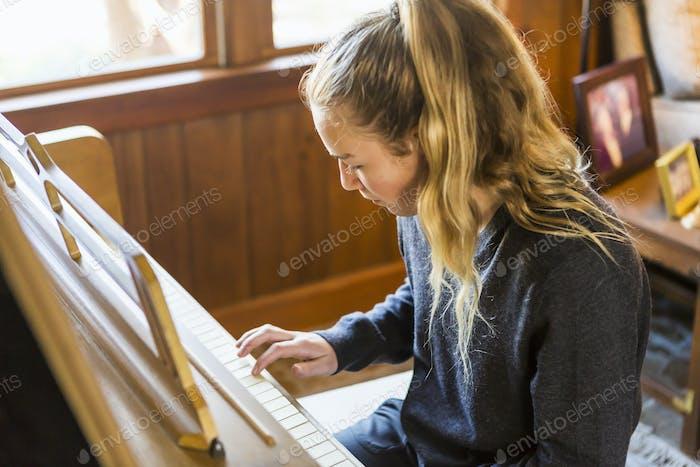 Teenager-Mädchen spielt Klavier, üben.
