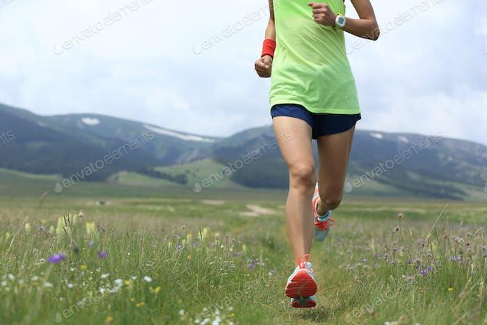 Runner running on grass trail