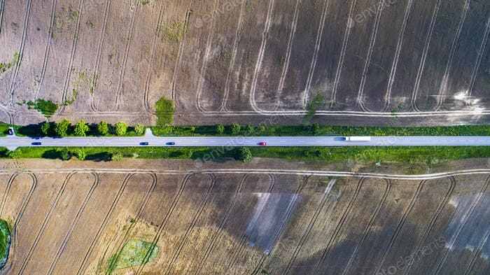 Aerial view of a road with cars between agricultural fields