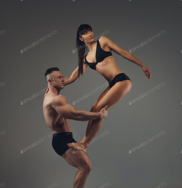 Shirtless muscular man holding slim brunette woman.