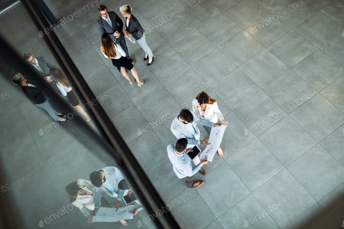 Modern business people walking on stairs in glass hall in office